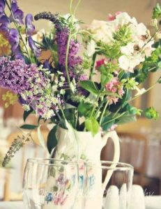 a jug of garden flowers in pretty and feminine colours.