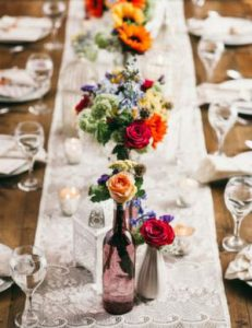 a close up of a table centre. a linen table runner is covered by bright vases of colourful flowers.