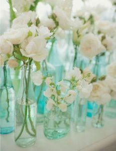 close up image of crisp white flowers in blue tinged glass vases.
