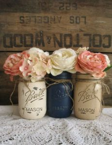 a cluster of 3 vintage containers containing david austin roses against a rustic backdrop