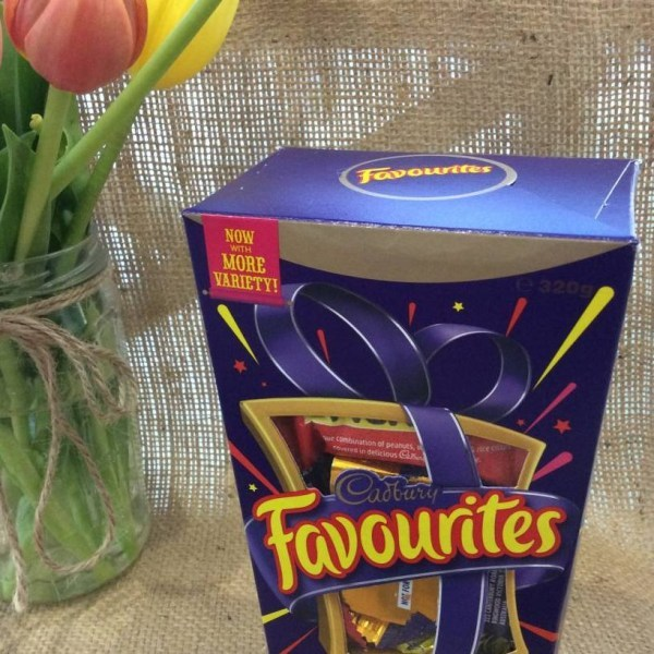 A box of Cadburys Favourites chocolates 320g with a jar of tulips in the background