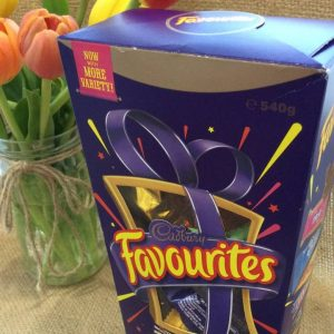 A large box of Cadburys Favourites chocolates 540g with a jar of tulips in the background
