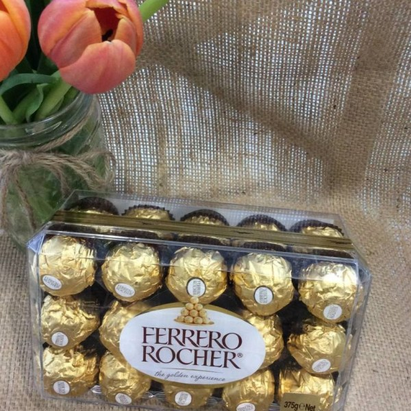 A box of Ferrero Rocher chocolates on a hessian background with a jar of tulips showing.