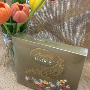 A 150g of Lindt chocolates on a hessian background with a jar of tulips shown behind.