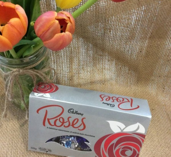 A 225g box of Cadburys Roses chocolates on a hessian background with a jar of tulips shown behind.