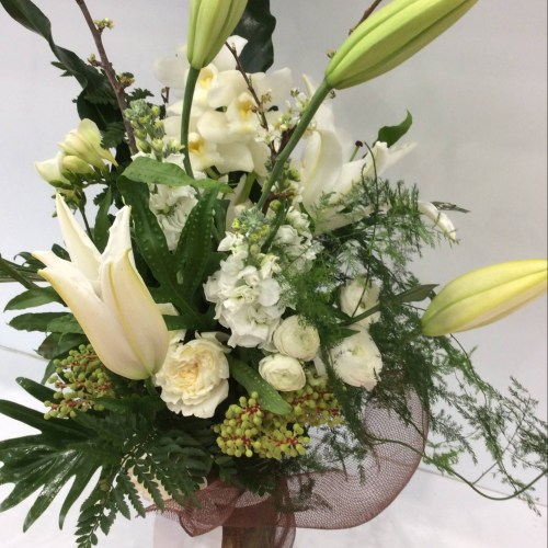 a sturctural vase arrangement of white seasonal flowers, sticks and loose floiages.