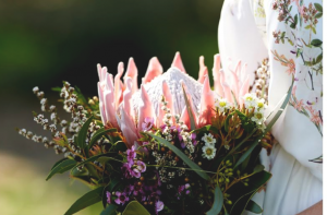 A professional image of a bridesmaid wearing a floral dress carrying a simple wildflower bouquet including a large king protea.