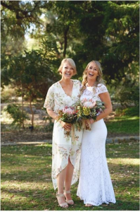 A professional photograph by Anthea Kirkham of a Bride and bridesmaid in kings park holding bouquets of king protea and wildflowers.