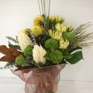 a white, green and yellow vase arrangement with sticks, magnolia leaves and netting.
