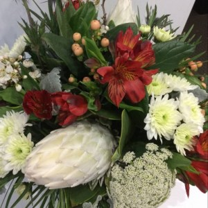 a white and red flower arrangement featuring king protea, alstromeria, hypericum berries and eryngium