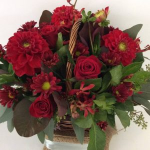 a wicker basket filled with red flowers.