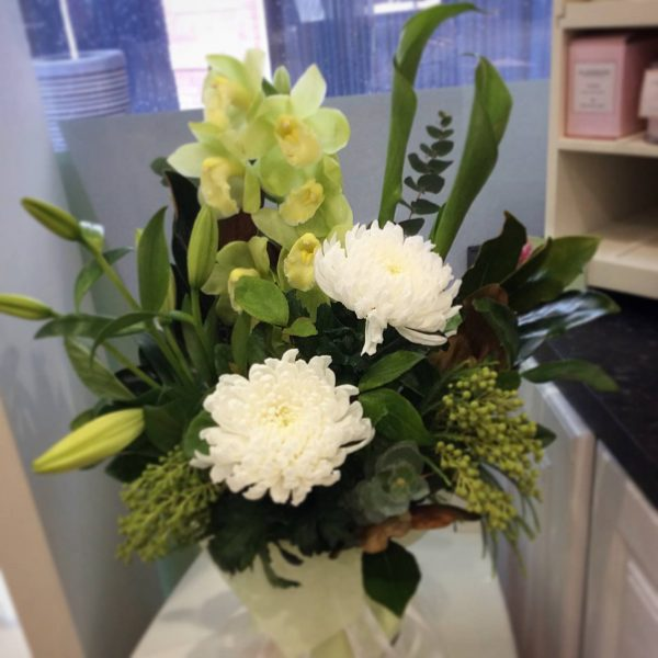 a vase arrangement of white disbuds, green cymbidium orchid, green godess and white lilies.