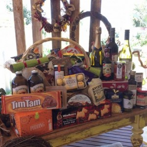 a table full of gourmet food items including wine, cheese, chocolates, christmas food items.