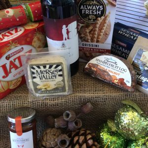 a secelection of wine, cheeses and crackers with christmas decorations