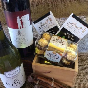 a bottle of red wine, a bottle of white wine, a box of ferrero rocher chocolates and two bars of lindt chocolate.