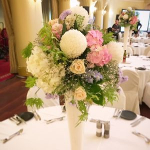 a tall centrepiece of pink, white and blue flowers in a round shape.