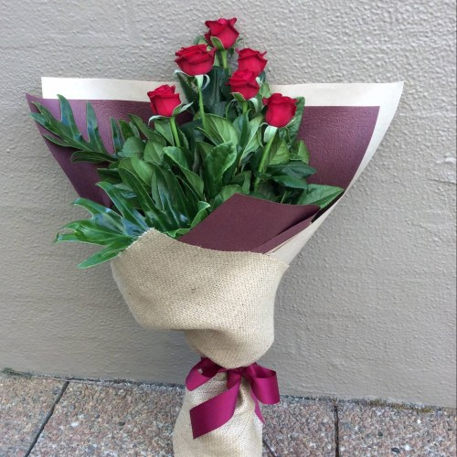 a hand tied bouquet of 6 red roses, wrapped in neutral paper and hessian- A Touch of Class Florist.