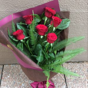 a hand tied bouquet of 6 red roses, wrapped in neutral paper and hessian.