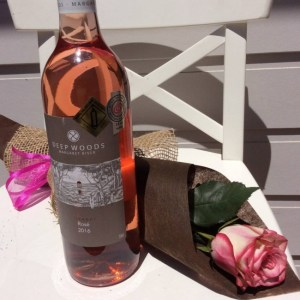 a single pink rose wrapped in neutral paper and hessian with a bottle of rosé wine- A Touch of Class Florist