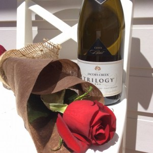 a single red rose wrapped in neutral paper and hessian with a bottle of sparkling wine- A Touch of Class Florist