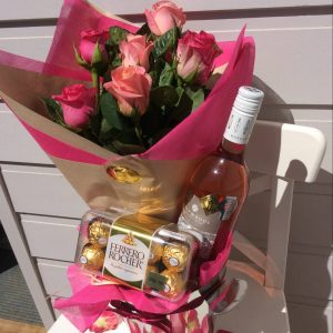 6 pink roses in a handtied bouquet, a bottle of rosé wine and a box of ferrero rocher chocolates in a stainless steel wine bucket