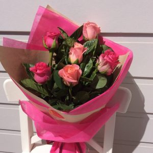 a hand tied bouquet of 6 pink roses, wrapped in neutral and pink paper and hessian.