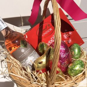 a wicker basket filled with lindt chocolates, a lindt bunny, cadburys eggs and a bottle of rosé wine