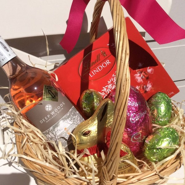 a wicker basket filled with lindt chocolates, a lindt bunny, cadburys eggs and a bottle of rosé wine- A Touch of Class Florist