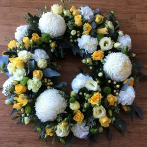 a large floral wreath in soft yellow and white.