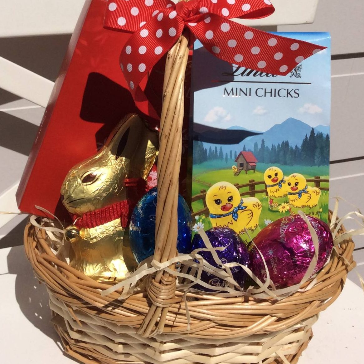 Basket of easter goodies a touch of class florist a wicker basket of chocolate eggs lindt chicks a lindt bunny negle Image collections