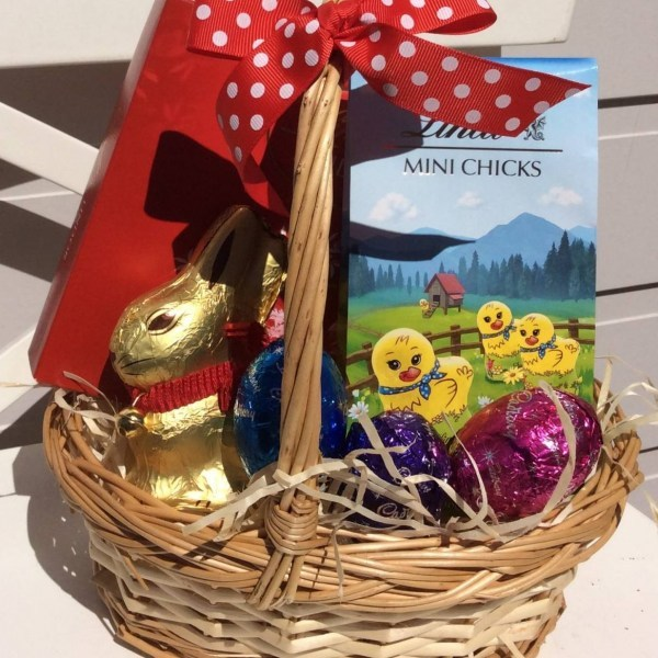 a wicker basket of chocolate eggs, lindt chicks, a lindt bunny.- A Touch of Class Florist