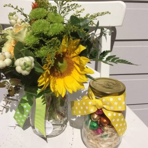a mason jar filled with mini easter eggs and a jar fliled with orange, yellow and green flowers.