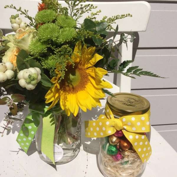 a mason jar filled with mini easter eggs and a jar fliled with orange, yellow and green flowers.- A Touch of Class Florist