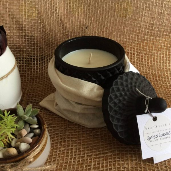 a bear and finn salted caramel scented candle in a black geo pot. pictured with two succulent pots.