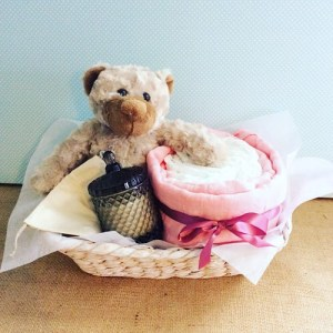 A Calm Change - This hamper contains a soft teddy bear, 10 newborn nappies, a muslin wrap, a bear and finn candle all wrapped up in a seagrass basket - A Touch of Class Florist