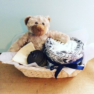 A Calm Change Hamper - contains a soft teddy, a muslin wrap, a Bear and Finn Candle and 10 newborn nappies all wrapped up in a seagrass basket - A touch of Class Florist