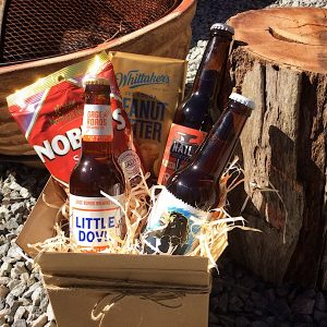 a cardboard box filled with 3 craft beer bottles, nobbys buts and whittakers chocolate bar. pictured next to an iron fire pit and wooden log.