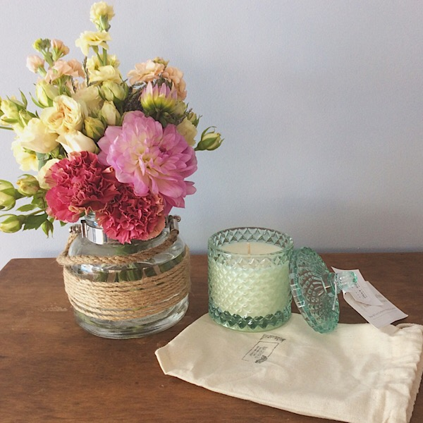 A sweet jar flower arrangement and a Bear and Finn scented candle in a green glass geo cut vanity jar- A Touch of Class Florist