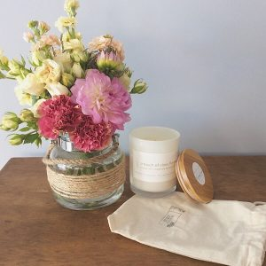 A sweet glass jar posy arrangement of seasonal blooms complimented with a bear and finn scented soy candle in glass pot with bamboo lid- A Touch of Class Florist