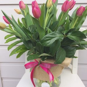 A Glass hurricane Vase arrangement of tulips
