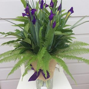 A glass cylinder vase arrangement of iris- A touch of Class Florist