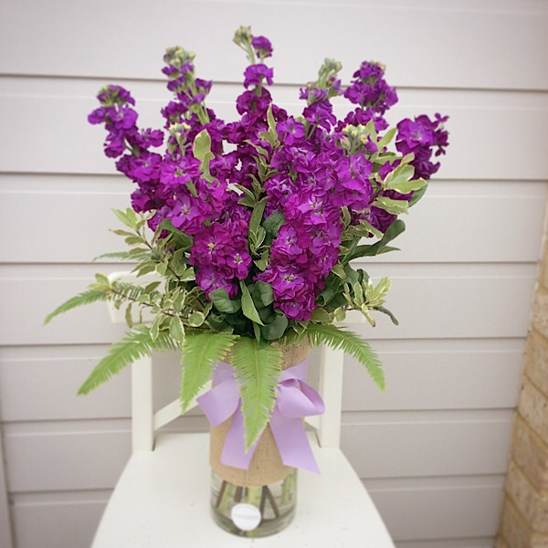 A glass vase arrangment of seasonal stocks- A touch of Class Florist