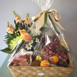 A fresh seasonal fruit and flower hamper gift wrapped in a basket