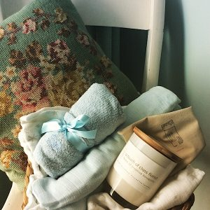 A baby gift hamper in blue. Contains a Bear and Finn soy candle, 2 baby wraps and a season suitable baby clothing item all giftwrapped in a basket.