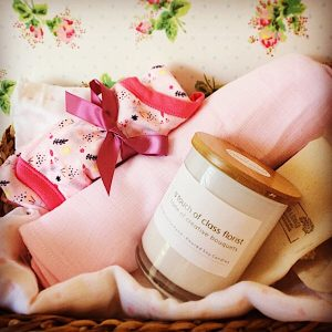 A newborn baby hamper in pink tones. Includes a Bear and Finn soy candle, 2 baby wraps and a seasonally suitable baby clothing item. Gift wrapped in a basket.