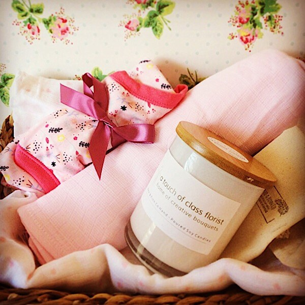 A newborn baby hamper in pink tones. Includes a Bear and Finn soy candle, 2 baby wraps and a seasonally suitable baby clothing item. Gift wrapped in a basket.- A Touch of Class Florist