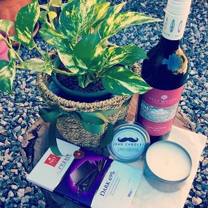 A hamper with wine, block of chocolate, a Bear and Finn man candle and a potted plant