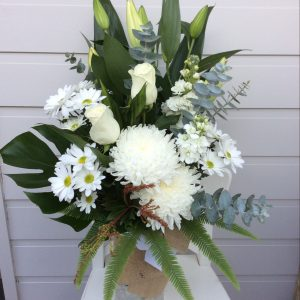a vase arrangement of white flowers and tropical leaves