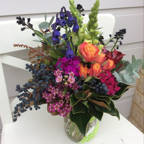 A bright jam jar vase arrangement of flowers - A Touch of Class Florist
