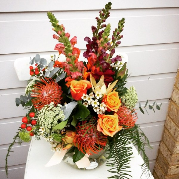 Easy Tiger Fishbowl Arrangement a fishbowl arrangement in orange red and white- A Touch of Class Florist
